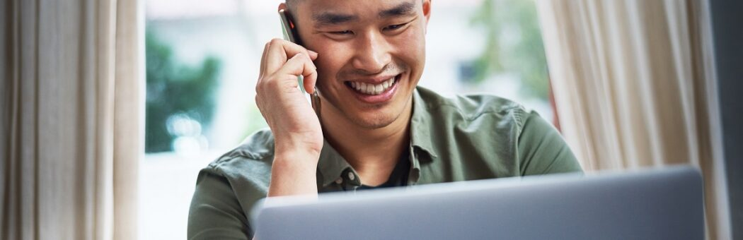 young man talking happily on phone