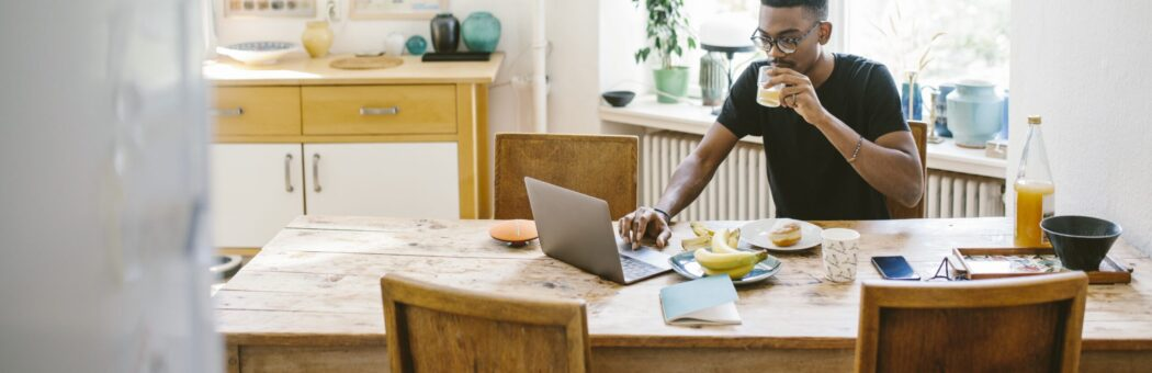 Man sat at dining table with laptop