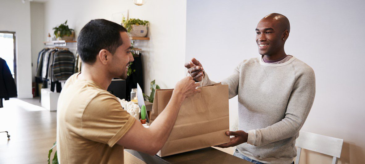 Man smiling to checkout assistant while buying an item in a shop