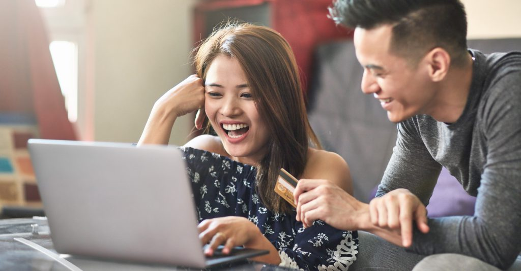 Happy couple shopping through laptop at home