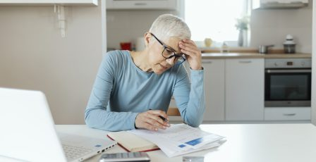 Older woman sitting in kitchen looking at paperwork