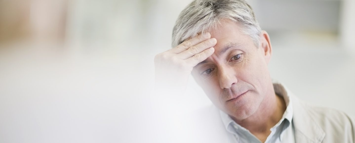 Man rubbing his head in anguish