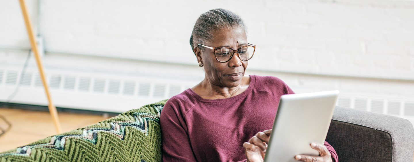 Senior woman relaxing whilst using a tablet