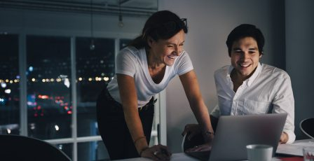 Two people working on a laptop